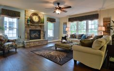 A welcoming living room with stacked stone fireplace and hardwood floors.  © 2014 Copyright. Ryan Homes