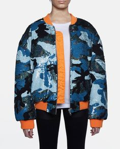 Blue camouflage sequin flight jacket with two zip closure pockets. Finished with orange cuffs and hem.