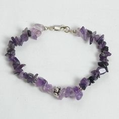 """Handmade gemstone amethyst bracelet features a strand of semi-precious amethyst gemstone chips, sterling silver accent beads, lobster claw clasp, and stretch band. 8"""" in length. Add a necklace, pendan"""