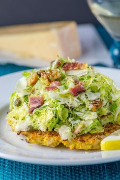 Shaved Brussels Sprouts Over Crispy Cauliflower Cakes - Thinly sliced Brussels sprouts slaw served over crispy cauliflower cakes, dressed in a lemon vinaigrette and topped with bacon and walnuts. A sensational salad made from two vegetables once considered boring and unglamorous!   QueenofMyKitchen.com