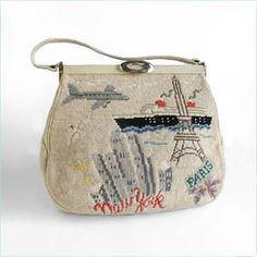 Beige, leather-trimmed needlepoint handbag with travel theme