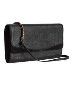 Black. Clutch in grained imitation leather with imitation suede details. Narrow, detachable shoulder strap in metal and imitation leather, flap with