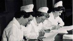 Head nurses writing their reports while wearing their John Hopkins graduate caps