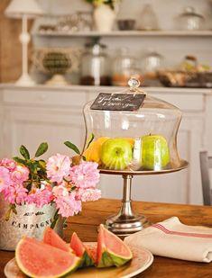 En la mesa Frutero de plata con tapa de cristal y plato de cerámica, similares de Becara. El mueble