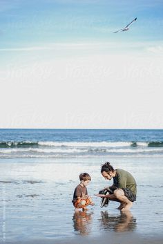 Boy and his dad together on a beach in summer by Cara Slifka