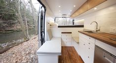 Van Ram Promaster Gets Kitchenette And Tesla Battery Tech Camper Van Conversion Companies, Tesla Power, Acacia Wood Flooring, Slider Window, Get Off The Grid, Ram Promaster, Full Size Mattress, Adventure Campers, Walnut Dining Table