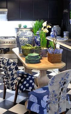small kitchen, blue and white, dark painted cabinets, checkerboard floor, chinoiserie, chair slipcovers, black cabinets, light natural wood kitchen table, #blueandwhite. Designed by Tessa Proudfoot.