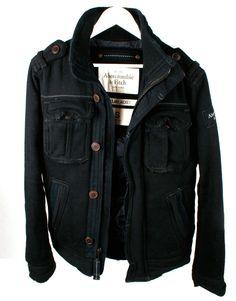 Abrigo negro, grueso, forrado. Multi bolsillos, con detalles en los hombros. Cremallera y botones centrales ocultos.