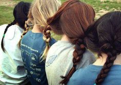Four Friends sitting together...with their hair braided with each other's hair tied in together....cool idea!