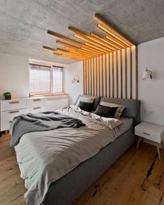 An amazing wooden headboard designed by  architect Indre Sunklodiene that extends into the ceiling to double as a light source.