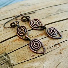 Handcrafted copper ear wires form a raindrop shaped swirls. Two larger copper raindrops hang below, making these earrings a total length of