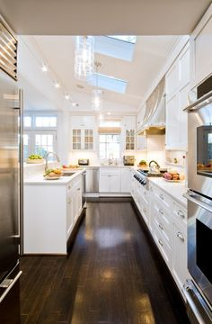Separate space for fridge and ovens, dark floors, white cabinets, skylights, sloped ceiling