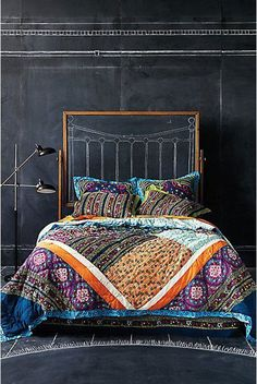 Diagonal quilt - bright colors contrast with dark walls and floor. Check out the use of a chalkboard easel for the headboard: you can draw one on there, or draw anything else for that matter.