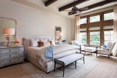 This master bedroom expertly employs French Country accents to soften the heavier wood trim of the ceiling and windows. Identical mirrors, ornate lamps and distressed nightstands balance the queen bed on either side, while the floor-length windows elongate and brighten the overall space.