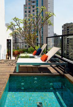 O deque de cumaru foi ampliado com a reforma da piscina, revestida de pastilhas, na cor verde-antilhas. Projeto publicado em Casa e Jardim.