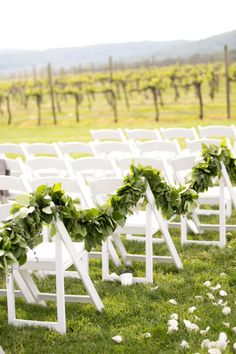Garlands of greenery will draped down the aisle, tied to the chairs with dripping nude-colored ribbons.