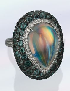 A 15.58 carat moonstone ring with colour-change garnets in daylight by James Currens