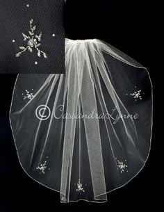 This simple bridal veil had an embroidered edge and five crystal and bead flower designs. It is 30 inches long and 72 inches wide, on a four inch metal comb. Th
