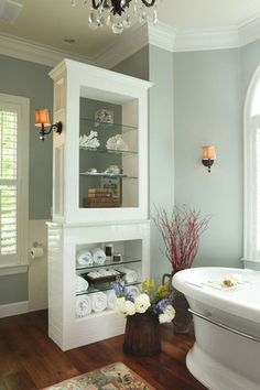 Traditional Master Bathroom with Arched window, Wall sconce, Wide plank walnut flooring, Crown molding, Freestanding