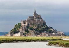 This is Mont Saint-Michel. It is an island commune in Normandy, France. Mont Saint-Michel is a medieval village with inhabitants living in there as well as a mayor. It has a population of 44 people. Mont Saint Michel France, Paris Travel, France Travel, Beautiful Castles, Beautiful Places, Amazing Places, St Michael's Mount, Day Trip From Paris, Brittany France