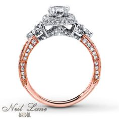 All the glamour of Hollywood can be hers with this vintage-inspired engagement ring from Neil Lane Bridal®. A breathtaking round diamond is framed in more round diamonds set in 14K white gold. Additional round diamonds dance along the band of 14K rose gold for a design that is truly divine. The ring has a total diamond weight of 1 5/8 carats and features Neil Lane's signature inside of the band. Diamond Total Carat Weight may range from 1.58 - 1.68 carats.