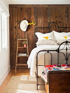 Salvaged wood creates a warm backdrop for an antique iron bed. A vibrant throw and printed pillows energize the vintage frame. A natural grass rug anchors the room, while funky painted antlers fashioned into hooks contribute contemporary flair. Cozy Bedroom, Bedroom Decor, Bedroom Ideas, Earthy Bedroom, Seaside Bedroom, Bedroom Romantic, Wooden Bedroom, Bedding Decor, Bedroom Retreat