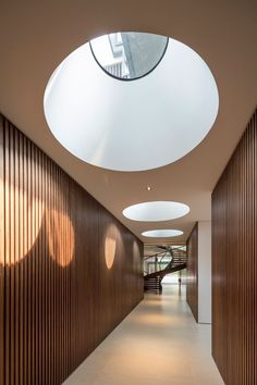 This wood lined hallway has large round skylights to introduce sunlight to the space.