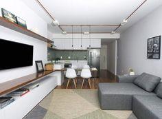 Projeto SP Estudio - A integração marca o projeto. Um dos destaques é a bancada de apoio da TV, que se estende até a cozinha, ganhando a função de mesa de jantar e de trabalho