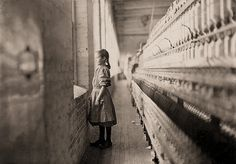 By Lewis W. Hine - The Mill: A moment's glimpse of the outer world. Said she was 11 years old. Been working over a year. Rhodes Mfg. Co. Lincolnton, North Carolina.