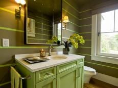 Silver scrollwork wallpaper makes this art deco-style powder room truly shine. Designer Susan Brunstrum further dressed up the bathroom with a Lucite vanity, metallic accents and pops of color throughout.