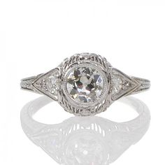 A platinum Art Deco ring featuring a central 0.52ct old cut diamond in a bezel mount with a single smaller diamond to either side within tapering millegrain edged mounts all above an arched and curved gallery featuring floral detail against a pierced geometric background all merging to an engraved band. #RutherfordJewellery #Melbourne