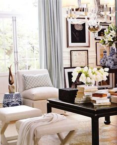 Living room- great ivory end benches, neutral chair, walls, and rugs, black lacquered coffee table, lucite chandelier, sea foam curtains and accent pillow