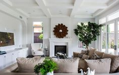 Transitional living room with coffered ceiling features a beige linen sectional facing a wood sunburst mirror above the fireplace between windows.