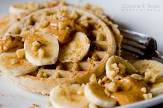 Organic flax waffles with warm peanut butter, banana slices, and chopped walnuts and a glass of 1% milk