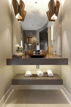 Fabulous feature wash basin wall lights give great lighting for the face.  LED linear lighting under the vanity unit and a mini downlight in the niche about the WC provide great background and night lighting