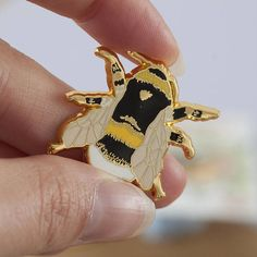 A beautiful British Bee Pin. A hard enamel pin, based on an illustration of a British White-Tailed Bumble Bee. Pop it on your collar, bag or coat to jazz up your outfit! Show your love for the British Bee, it needs your help! Presented on a backing card, this pin measures 3 cm