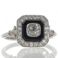 A platinum octagonal plaque ring featuring a 0.55ct old cushion cut diamond graded as colour I-J clarity SI2 in a bezel setting on an onyx plaque surrounded by a border of twenty old cut diamonds grain set all to a pierced under bezel and a triple wire band with trefoil shaped shoulders. #rutherfordjewellery