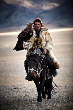 A mongolian hunter on a riding horse armed with a Golden Eagle.  Photographer Unknown