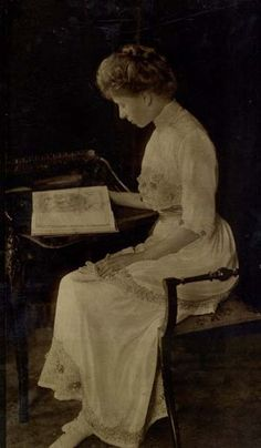 Vintage photograph of Princess Mary (1867-1953) Queen Consort of the United Kingdom 1910-36, wife of King George V, shown in a full-length pose seated at a desk reading a book, taken at Buckingham Palace