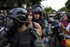 Venezuela's national guards detain an anti-government protester during a protest against President Nicolas Maduro's government in Caracas May 12, 2014.