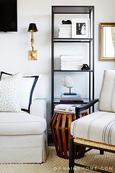 Total Makeover: Inside Our Co-Founder Katherine Power's Elegant New Office // white linen sofa, bordered throw pillow, gray leopard-print pillow, ticking stripe armchair, linear wooden stool, black bookcase, brass sconce, brass mirror