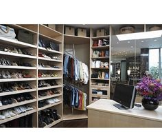 This custom walk-in closet features large mirrors and an assortment of storage options for shoes, clothing, bags, and more. Design by http://laclosetdesign.com/