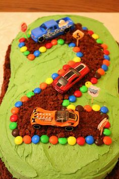 Car themed birthday cake. 2 round cakes joined together, cutting an inch or two so off one side of each so they join together. Crumble up the cut off pieces to make the road and a border around the cake. Tidy up the edges with mm's! This was so easy to make since I am completely incapable of using a piping bag.