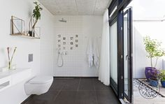The minimalist bathroom of the Forrest House near Aarhus, Denmark. It's dressed up with unique art tiles in the shower.