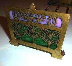"""Arts and Crafts/Art Nouveau Expandable Book Rack With Slag Glass Inserts. This is a desk top expandable book rack. The cast brass end plates feature a filigree design of flowers and leaves which skirts both Art Nouveau and Art Nouveau styles in my opinion. Behind the cast filigree designs are pieces of pink and green slag glass backed by a sheet brass plate. The end plates are 3 1/2""""H X 4 1/2""""W. The usable space between the end plates measures 12 1/2""""-23"""", depending on how far the ends are…"""