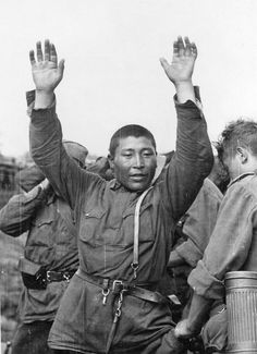 Central Asian Red Army conscript is searched by German troops after being taken POW on the sector of the 16th German Army, part of Army Group North, summer 1941.
