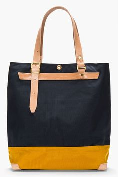 "MASTER-PIECE Co //  Navy Bi-Color Leather-trimmed DUO tote  32401M142001  Textile tote in navy and dark yellow. Leather trimmings throughout in beige. Brass hardware. Two leather carry handles with pin buckles at top. Patch pocket with leather detail at face. Snap button closure at main compartment. Zip pocket and patch pocket at bag interior. Reinforced base. Tonal stitching. Approx 15"" length x 16"" height x 5.5"" width. Made with Cordura fabric. Made in Japan.  $225 CAD"