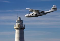 Armed Forces Day 2014 (Newtownards Airfield). Consolidated Catalina G-PBYA Flying past Donaghadee Lighthouse, County Down, Northern Ireland.