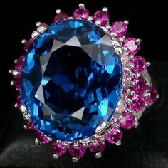 Marvelous Swiss Blue Topaz (16mm x 14mm) totaling 14 carats is framed by 20-2mm Pink Sapphires and then 22-2.3mm Pink Rubies set in sterling. A delicious piece! This ring can be sized by a good jewele