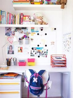 White desk and chair with desk organiser, pinboard above and wall shelf, child's rucksack on back of chair